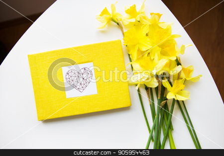 Yellow bouquet of daffodils and yellow book on white table stock photo, Yellow bouquet of daffodils and yellow book on white table. by Sergiy Artsaba