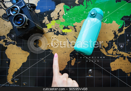 Map of the world in Russian. The finger of the girl points to different corners of the world. stock photo, Map of the world in Russian. The finger of the girl points to different corners of the world by Sergiy Artsaba