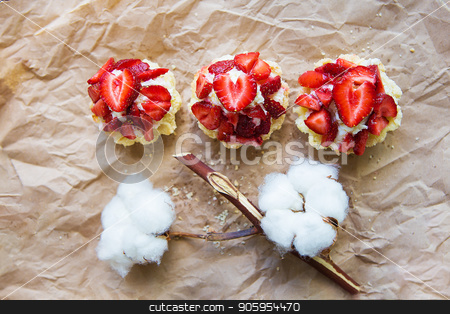 Beautiful cupcakes with strawberries along with a branch of cotton lies on kraft paper stock photo, Beautiful cupcakes with strawberries along with a branch of cotton lies on kraft paper. by Sergiy Artsaba
