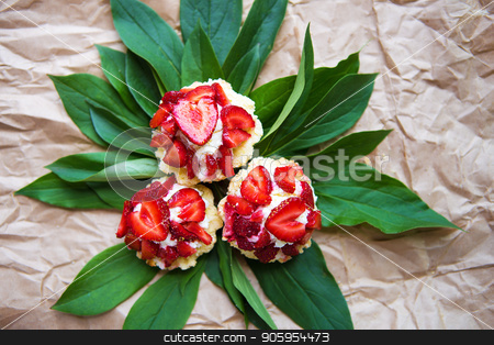 Beautiful and bright cupcakes with strawberries lie on green leaves, close-up stock photo, Beautiful and bright cupcakes with strawberries lie on green leaves, close-up. by Sergiy Artsaba