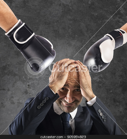 Businessman receives fists from competitors. concept of difficult career stock photo, Injustice for an businessman that receives fists from competitors. concept of difficult career by Federico Caputo