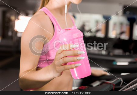 woman at the treadmill with a shaker stock photo, slim woman standing on the running track in the gym wearing earphones listening to music and holding a shaker with protein. Concept of cardio exercises and healthy way of life by Oleh