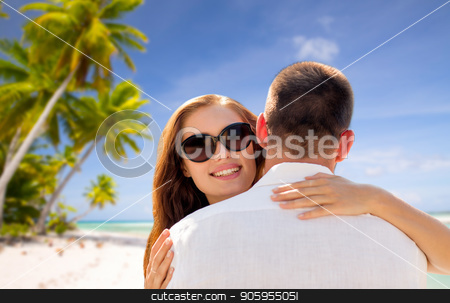 happy couple hugging over tropical beach stock photo, travel, tourism and summer vacation concept - happy couple hugging over tropical beach background in french polynesia by Syda Productions