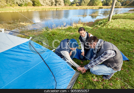 happy parents and son setting up tent at campsite stock photo, camping, tourism and family concept - happy mother, father and son setting up tent at campsite by Syda Productions