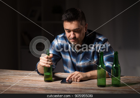 man with smartphone and bottle of beer at night stock photo, alcoholism, alcohol addiction and people concept - drunk man with smartphone and bottle of beer at night by Syda Productions