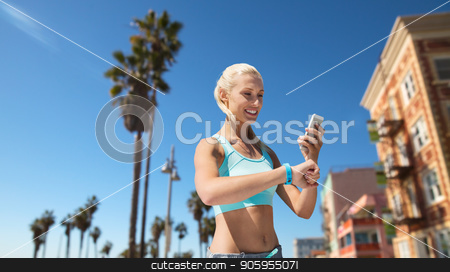 happy woman with fitness tracker and smartphone stock photo, sport, technology and healthy lifestyle concept - smiling young woman with fitness tracker and smartphone exercising over venice beach background in california by Syda Productions