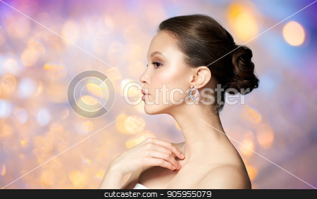close up of beautiful woman face with earring stock photo, beauty, jewelry, people and luxury concept - close up of beautiful asian woman face with earring over holidays lights background by Syda Productions