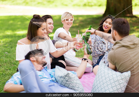 friends clinking drinks at picnic in summer park stock photo, leisure, people and celebration concept - happy friends clinking non alcoholic drinks at picnic in summer park by Syda Productions