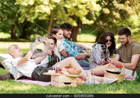 friends with smartphones on picnic at summer park stock photo, friendship, leisure, technology and people concept - group of friends with smartphones chilling on picnic blanket and drinking non alcoholic beer at summer park by Syda Productions