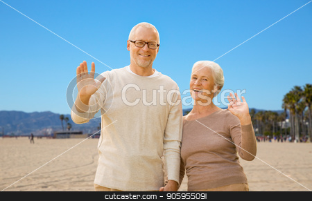 happy senior couple waving hands over venice beach stock photo, old age, travel and tourism and people concept - happy senior couple waving hands over venice beach background in california by Syda Productions