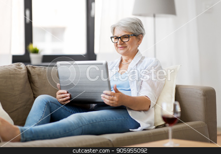 senior woman with on laptop resting at home stock photo, technology, old age and people concept - happy senior woman in glasses with laptop computer and glass of wine at home by Syda Productions