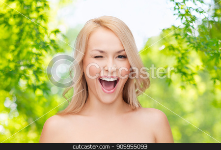 beautiful woman over green natural background stock photo, people and beauty concept - beautiful smiling young woman winking over green natural background by Syda Productions
