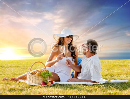 smiling couple drinking champagne at picnic stock photo, love, dating, people and celebration concept - smiling couple drinking champagne at picnic on meadow over sunset sky background by Syda Productions