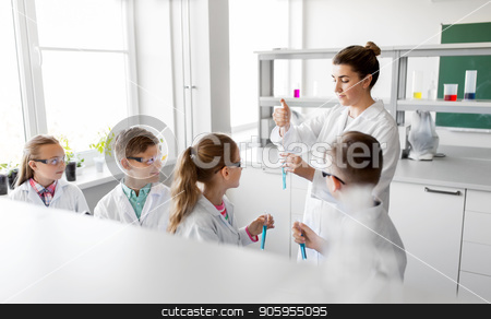 teacher and students studying chemistry at school stock photo, education, science and children concept - teacher and kids or students with test tubes studying chemistry at school laboratory by Syda Productions