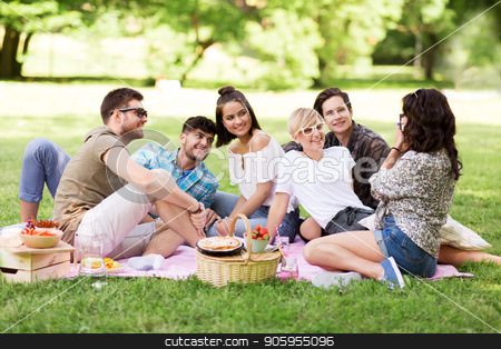 friends photographing at picnic in summer park stock photo, friendship, leisure and technology concept - group of happy smiling friends photographing at picnic in summer park by Syda Productions