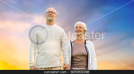 happy senior couple holding hands over evening sky stock photo, old age, tourism, travel and people concept - happy senior couple holding hands over evening sky background by Syda Productions
