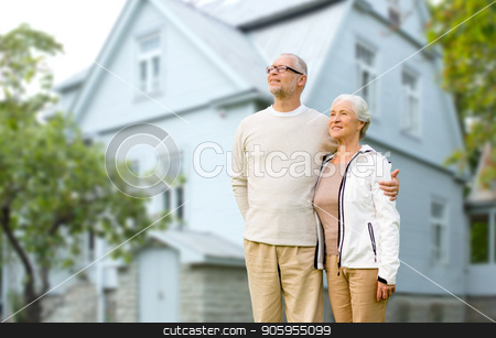 happy senior couple hugging over house background stock photo, old age, accommodation and real estate concept - happy senior couple hugging over house background by Syda Productions