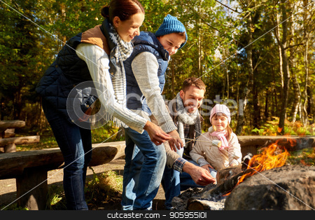 happy family roasting marshmallow over campfire stock photo, camping, travel, tourism, hike and people concept - happy family roasting marshmallow over campfire by Syda Productions