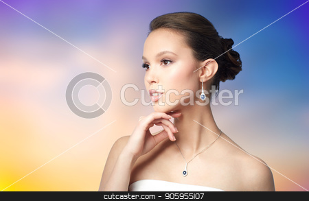 beautiful asian woman with earring and pendant stock photo, beauty, jewelry, people and luxury concept - beautiful asian woman or bride with earring and pendant over pastel background by Syda Productions