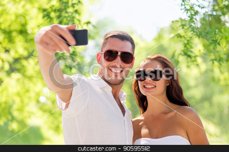 couple making selfie over natural background stock photo, love, summer and technology concept - smiling couple in sunglasses making selfie by smartphone over green natural background by Syda Productions