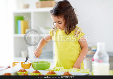 little girl baking muffins at home stock photo, family, cooking, baking and people concept - little girl making batter for muffins or cupcakes at home kitchen by Syda Productions