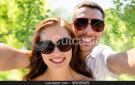 smiling couple wearing sunglasses making selfie stock photo, love, summer and people concept - smiling couple wearing sunglasses making selfie over green natural background by Syda Productions