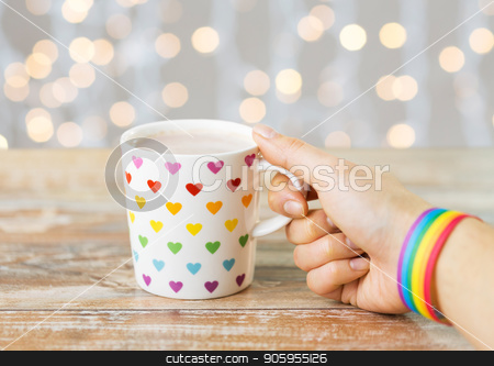 hand with cup of cacao and gay awareness wristband stock photo, homosexual and lgbt concept - female hand with cacao drink in cup with rainbow colored heart pattern and gay pride awareness wristband with festive lights background by Syda Productions