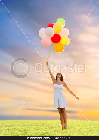 woman in sunglasses with balloons over sunset sky stock photo, happiness, summer and people concept - smiling young woman wearing sunglasses with balloons on meadow over sunset sky background by Syda Productions