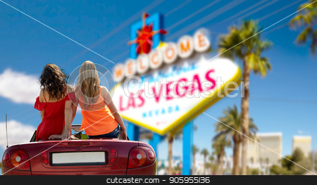 friends driving in convertible car at las vegas stock photo, summer holidays, road trip and travel concept - happy friends driving in convertible car over welcome to fabulous las vegas sign background by Syda Productions