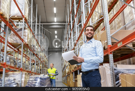 happy businessman with clipboard at warehouse stock photo, logistic business, shipment and people concept - happy businessman or manager with clipboard and loader at warehouse by Syda Productions