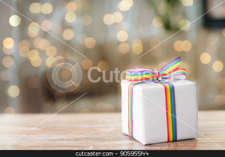 present with gay awareness ribbon on table stock photo, homosexual and lgbt concept - gift box with gay pride awareness ribbon on wooden table over festive lights background by Syda Productions