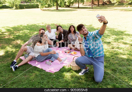 friends taking selfie by smartphone at picnic stock photo, friendship, leisure and technology concept - group of happy smiling friends taking selfie by smartphone chilling on picnic blanket at summer park by Syda Productions