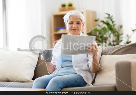 senior woman with coffee reading newspaper at home stock photo, old age, leisure and people concept - happy senior woman drinking coffee or tea and reading newspaper at home by Syda Productions