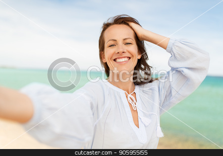 happy smiling woman taking selfie on summer beach stock photo, summer holidays and leisure concept - happy smiling woman taking selfie on beach by Syda Productions