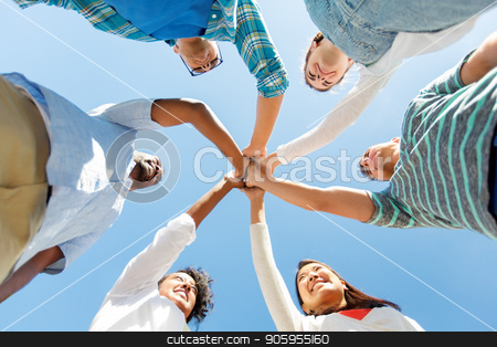 happy smiling friends outdoors standing in circle stock photo, people, friendship and international concept - group of happy smiling friends outdoors standing in circle by Syda Productions