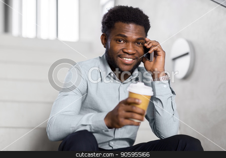 businessman calling on smartphone at office stairs stock photo, business, technology, communication and people concept - african american businessman calling on smartphone and drinking coffee at office stairs by Syda Productions