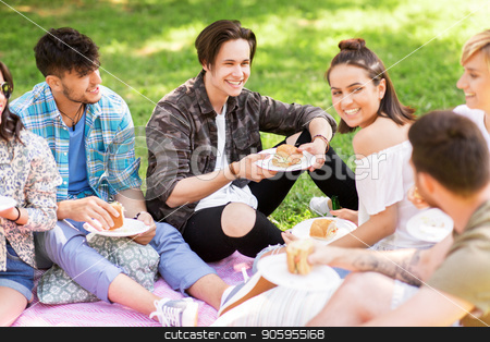 happy friends eating sandwiches at summer picnic stock photo, friendship, leisure and fast food concept - group of happy friends eating sandwiches or burgers at picnic in summer park by Syda Productions