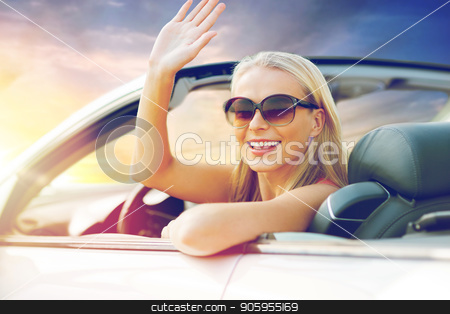 happy young woman in convertible car waving hand stock photo, travel, road trip and people concept - happy young woman in convertible car waving hand over sunset sky background by Syda Productions