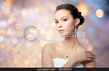 beautiful asian woman with earring and pendant stock photo, beauty, jewelry, people and luxury concept - beautiful asian woman or bride with earring and pendant over holidays lights background by Syda Productions