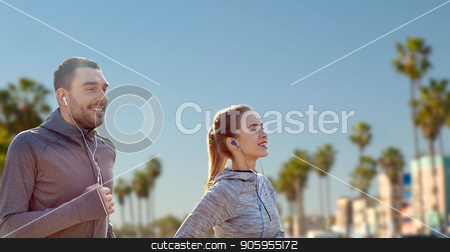 couple with earphones running over venice beach stock photo, fitness, sport and technology concept - happy couple running and listening to music in earphones over venice beach background in california by Syda Productions
