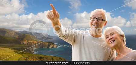 happy senior couple over big sur coast stock photo, old age, tourism, travel and people concept - happy senior couple over bixby creek bridge on big sur coast of california background by Syda Productions