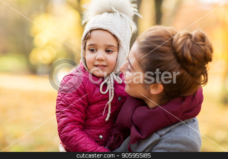 happy mother with little daughter at autumn park stock photo, family, season and people concept - happy mother holding little daughter at autumn park by Syda Productions