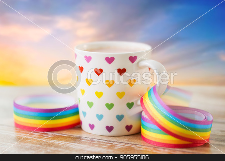cup with heart pattern and gay awareness ribbon stock photo, homosexual and lgbt concept - close up of cup with rainbow colored heart pattern and gay pride awareness ribbon on wooden table over evening sky background by Syda Productions
