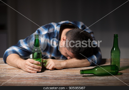 drunk man with beer bottles on table at night stock photo, alcoholism, alcohol addiction and people concept - male alcoholic with beer bottles lying or sleeping on table at night by Syda Productions