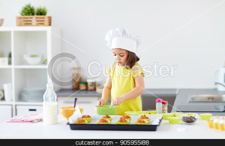 little girl in chefs toque baking muffins at home stock photo, family, cooking, baking and people concept - little girl in chefs toque making batter for muffins or cupcakes at home kitchen by Syda Productions