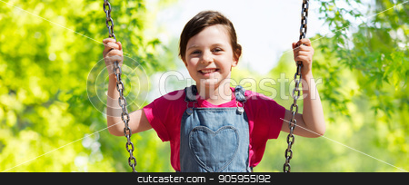 girl swinging on swing over natural background stock photo, childhood, leisure and summer concept - happy little girl swinging on swing over green natural background by Syda Productions