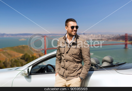 happy man near convertible car outdoors stock photo, road trip, travel and people concept - happy man near convertible car over golden gate bridge in san francisco bay background by Syda Productions