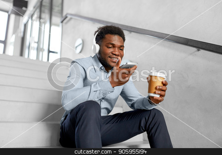 businessman records voice by smartphone at office stock photo, business, communication and technology concept - african american businessman in headphones calling or using voice recorder on smartphone at coffee break on office stairs by Syda Productions