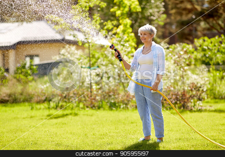 senior woman watering lawn by hose at garden stock photo, gardening and people concept - happy senior woman watering lawn by garden hose at summer by Syda Productions