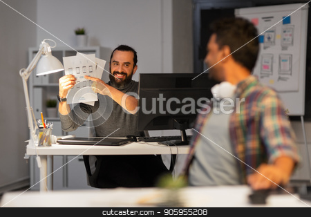 creative man showing papers to colleague at office stock photo, business, deadline and web design people concept - happy creative man showing papers to colleague at night office by Syda Productions